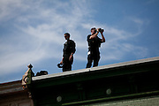 """Security on building roofs in Troy, Ohio scans the crowd during republican presidential candidate Mitt Romney campaign's """"Every Town Counts"""" bus tour."""