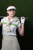 Woman with visor holding golf club behind shoulders portrait