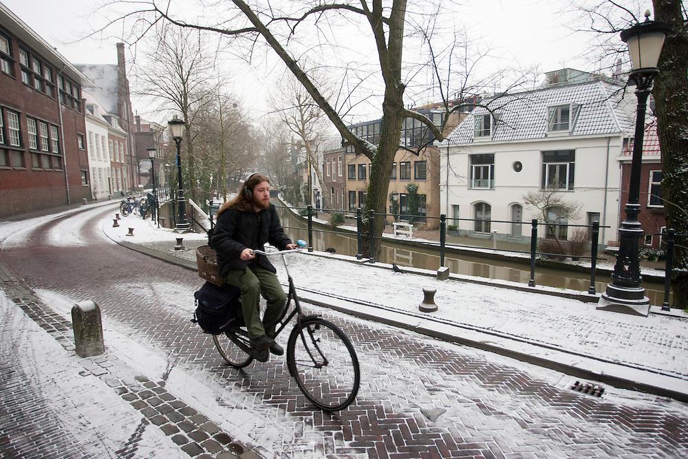 Een fietser rijdt door de een dun laagje sneeuw. Utrecht is bedekt met een heel dun laagje sneeuw.<br /> <br /> A cyclist is riding in the first snow in Utrecht.