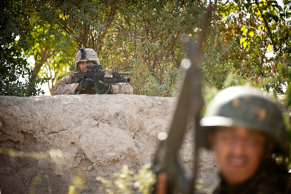 Marines and Afghan National Army soldiers react to sniper fire.