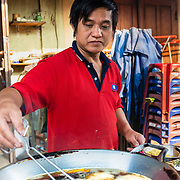 Lao man cooking street snacks at a morning market in Luang Prabang
