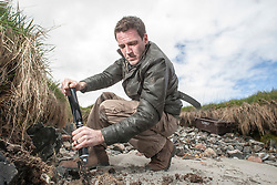 Historian Ashley Cowie digs on a beach, on Iona, during his road trip. He is doing a seven part series for The Scottish Sun on Scotland's treasure hunts at the end of April..©Michael Schofield..