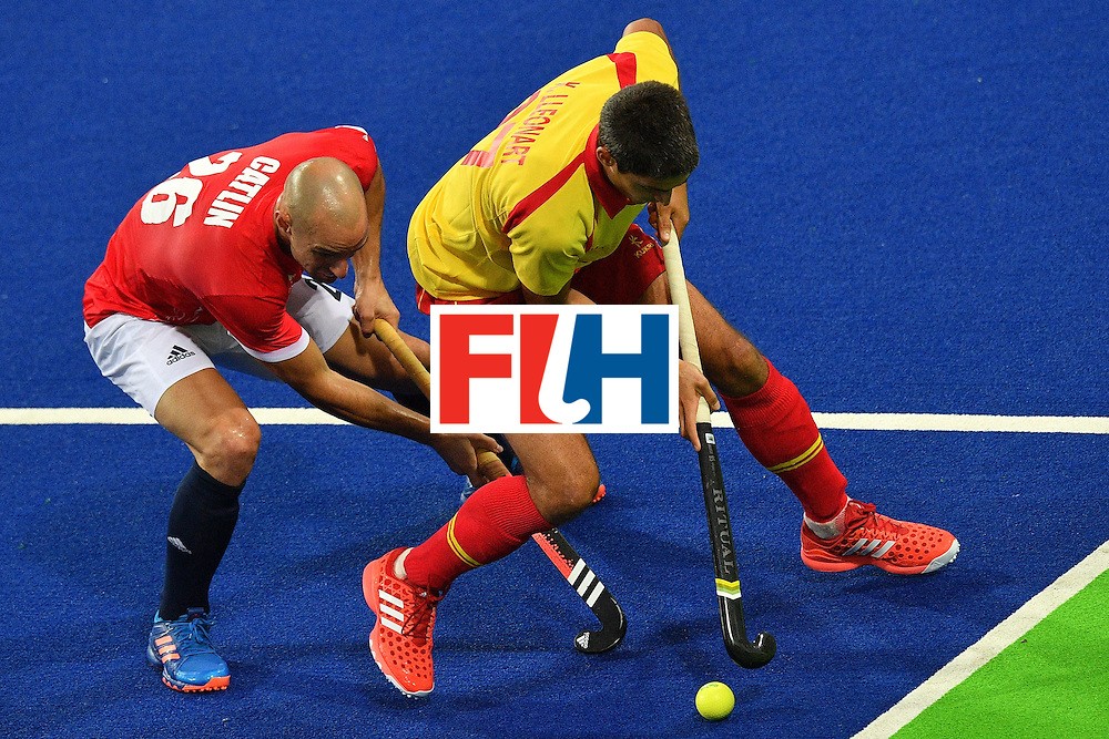 Spain's Xavi Lleonart (R) and Great Britain's Nick Catlin vie during the mens's field hockey Britain vs Spain match of the Rio 2016 Olympics Games at the Olympic Hockey Centre in Rio de Janeiro on August, 12 2016. / AFP / Carl DE SOUZA        (Photo credit should read CARL DE SOUZA/AFP/Getty Images)