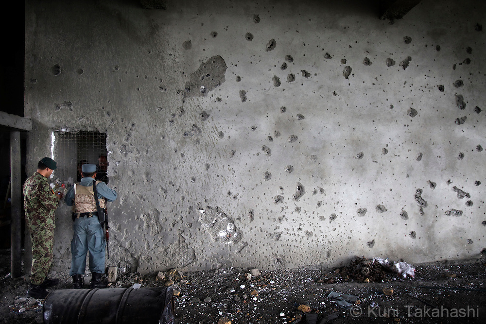 Afghan soldier and policeman stand in front of bullet-holed wall in the building near the U.S Embassy in Kabul, Afghanistan on Sep 14, 2011, where several insurgents were killed during an operation by Afghan and NATO coalition forces. Terrorists attacked multiple locations including U.S. Embassy and a nearby NATO base in Kabul..(Photo by Kuni Takahashi) .