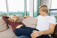 Serious couple looking at each other on sofa at home