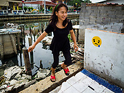 "22 MARCH 2018 - BANGKOK, THAILAND: A woman walks past where her home used to be on Khlong Lat Phrao. She can't afford the alternative housing city officials arranged for her. Bangkok officials are evicting about 1,000 families who have set up homes along Khlong  Lat Phrao in Bangkok, the city says they are ""encroaching"" on the khlong. Although some of the families have been living along the khlong (Thai for ""canal"") for generations, they don't have title to the property, and the city considers them squatters. The city says the residents are being evicted so the city can build new embankments to control flooding. Most of the residents have agreed to leave, but negotiations over compensation are continuing for residents who can't afford to move.      PHOTO BY JACK KURTZ"
