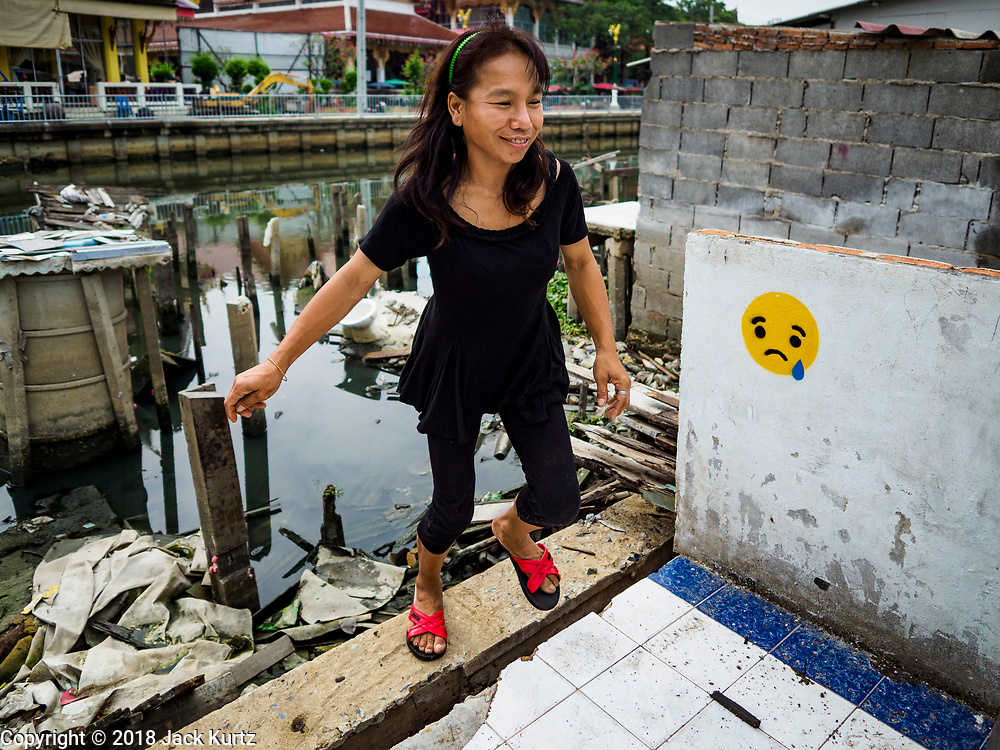 """22 MARCH 2018 - BANGKOK, THAILAND: A woman walks past where her home used to be on Khlong Lat Phrao. She can't afford the alternative housing city officials arranged for her. Bangkok officials are evicting about 1,000 families who have set up homes along Khlong  Lat Phrao in Bangkok, the city says they are """"encroaching"""" on the khlong. Although some of the families have been living along the khlong (Thai for """"canal"""") for generations, they don't have title to the property, and the city considers them squatters. The city says the residents are being evicted so the city can build new embankments to control flooding. Most of the residents have agreed to leave, but negotiations over compensation are continuing for residents who can't afford to move.      PHOTO BY JACK KURTZ"""