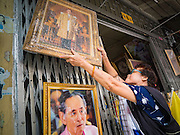 18 OCTOBER 2016 - BANGKOK, THAILAND: A shopkeeper hangs a display portrait of Bhumibol Adulyadej, the King of Thailand, in front of her shop. The King died Oct. 13, 2016. He was 88. His death came after a period of failing health. Bhumibol Adulyadej was born in Cambridge, MA, on 5 December 1927. He was the ninth monarch of Thailand from the Chakri Dynasty and is also known as Rama IX. He became King on June 9, 1946 and served as King of Thailand for 70 years, 126 days. He was, at the time of his death, the world's longest-serving head of state and the longest-reigning monarch in Thai history.     PHOTO BY JACK KURTZ