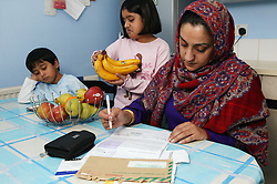 Single parent preparing to pay bills; with her children in her kitchen at home,