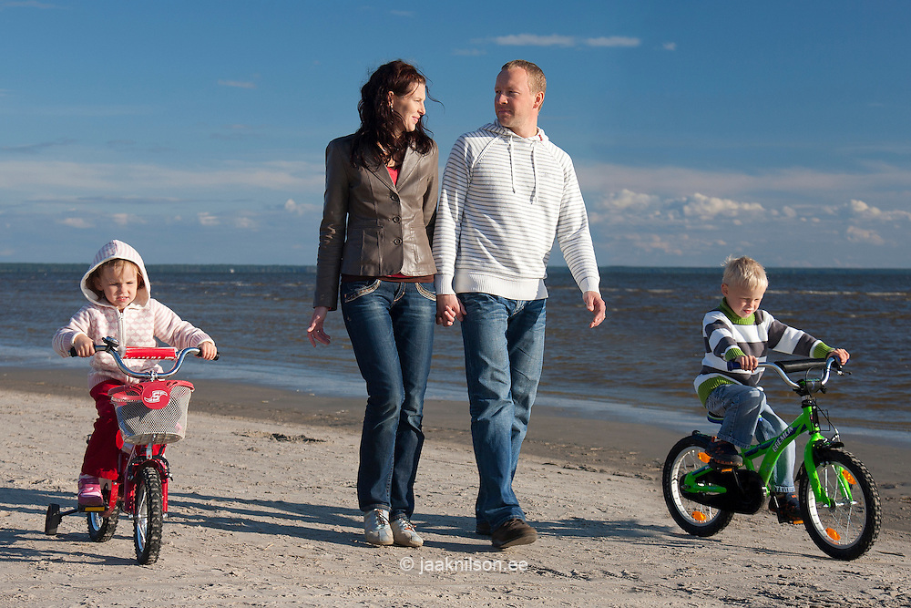 Young Family Walking with Kids on Bicycles on Pärnu Beach, Estonia