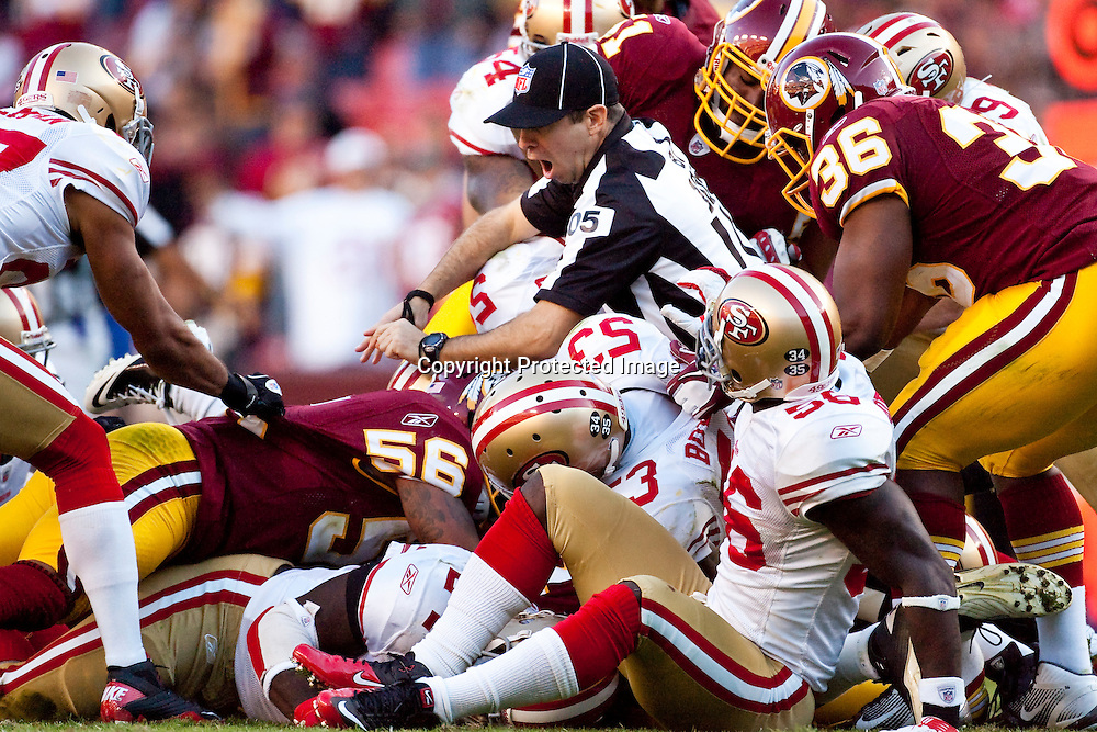 A referee gets caught in a pile-up between the Washington Redskins and the San Francisco 49ers at FedEx Field in Landover, Maryland.