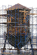 old rusty metal water tower with graffiti standing in scaffolding