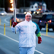 An Olympic torch runner moves along the Sea to Sky Highway, on it's way to Whistler