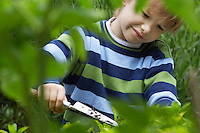 Boy (5-6) digging using trowel in countryside