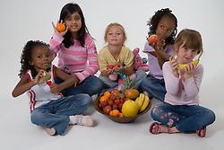 Group of children holding fruit,