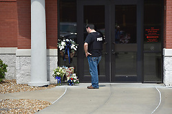 August 7, 2017 - Clinton, Missouri, U.S. - Flowers in memory of officer Gary Michael have been placed at the front door to the Clinton Police Department. Michael on Sunday night became the first Clinton officer to die in the line of duty. A manhunt is on for a suspect, who allegedly shot the officer. (Credit Image: © Keith Myers/TNS via ZUMA Wire)