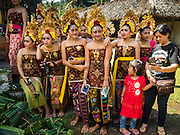 22 JULY 2016 - TENGANAN DUAH TUKAD, BALI, INDONESIA: Young women wait for the pandanus fights to begin in the Tenganan Duah Tukad village on Bali. The ritual Pandanus fights are dedicated to Hindu Lord Indra. Men engage in ritual combat with spiky pandanus leaves and rattan shields. They usually end up leaving bloody scratches on the combatants' backs. The young girls from the community wear their best outfits to watch the fights. The fights have been traced to traditional Balinese beliefs from the 14th century CE. The fights are annual events in the Balinese year, which is 210 days long, or about every seven months in the Gregorian calendar.    PHOTO BY JACK KURTZ