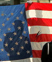 Firefighters hold a tattered U.S. flag found at the site of the World Trade Center disaster at a memorial service at Ground Zero on the fourth anniversary of the attack in New York September 11, 2005.