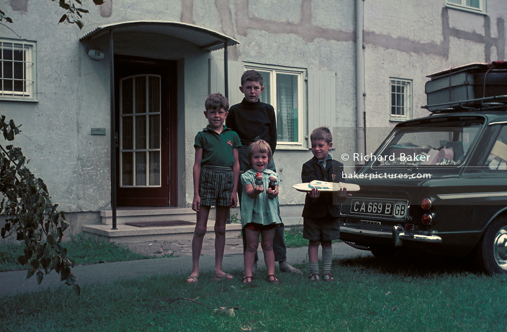 Children in Germany stand in front of a house next to a British Army-registered Singer Chamois (aka Hillman Imp) car, on 13th July 1970, in Lippstadt, Germany.