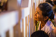 "03 FEBRUARY 2013 - PHNOM PENH, CAMBODIA:  A Cambodian woman looks through the wall surrounding the National Museum to watch the final Buddhist chanting service for former Cambodian King Norodom Sihanouk in the crematorium built for the King's funeral at the National Museum in Phnom Penh. Norodom Sihanouk (31 October 1922 - 15 October 2012) was the King of Cambodia from 1941 to 1955 and again from 1993 to 2004. He was the effective ruler of Cambodia from 1953 to 1970. After his second abdication in 2004, he was given the honorific of ""The King-Father of Cambodia."" He served as puppet head of state for the Khmer Rouge government in 1975-1976, before going into exile. Sihanouk's actual period of effective rule over Cambodia was from 9 November 1953, when Cambodia gained its independence from France, until 18 March 1970, when General Lon Nol and the National Assembly deposed him. Upon his final abdication in 2004, the Cambodian throne council appointed Norodom Sihamoni, one of Sihanouk's sons, as the new king. Sihanouk died in Beijing, China, where he was receiving medical care, on Oct. 15, 2012. His cremation will take place on Feb. 4, 2013. Over a million people are expected to attend the service.    PHOTO BY JACK KURTZ"
