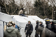 March 1, 2016 - Calais, France -<br /> <br /> Destruction Of Calais Jungle Camp Continues<br /> <br /> Policemen stand next to migrants on shelters roof as agents dismantle shacks on March 1, 2016 in the ''Jungle'' migrant camp in the French northern port city of Calais. Authorities return to clear migrant shelters from more parts of the 'Jungle' migrant camp in Calais and try to move people to shipping containers on another part of the site. French demolition teams began dismantling huts yesterday. Resistance is expected to continue and overnight riot police fired teargas at migrants who were throwing stones. A court ruling on Thursday approved a French Govt plan to clear part of the site. Authorities say approx 1,000 migrants are to be affected out of 3,700 people - many of them refugees from Syria and Iraq - who are thought to live in the camp. Mayor of Calais Natacha Bouchart has demanded the closure of the site for several weeks following several recent clashes with police  <br /> ©Exclusivepix Media