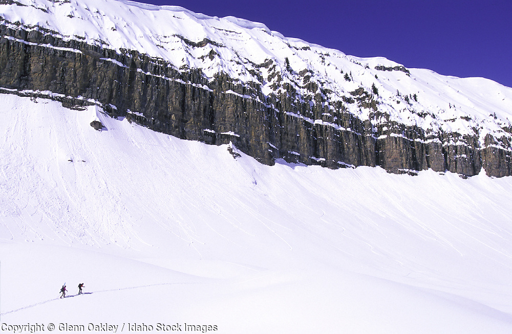 Skier and snowboarder below mtn. wall, Teton Mountains, Wyoming. MR