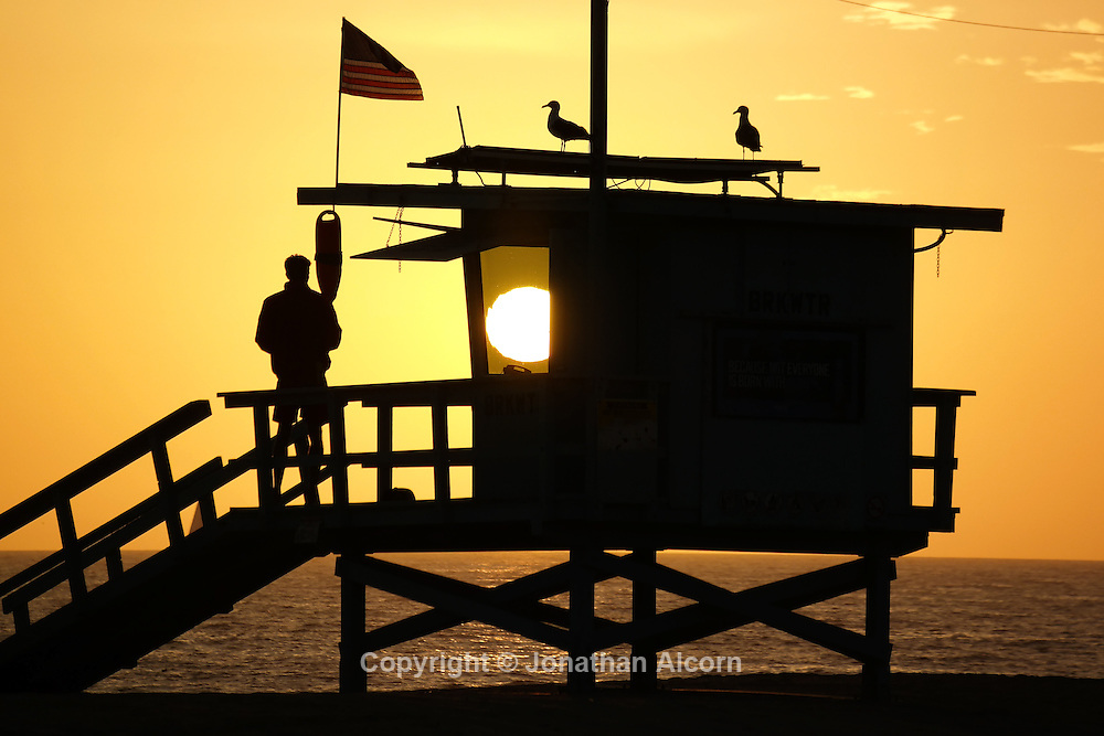 A lifeguard stands on watch as the setting sun is seen through a window on the tower on another day of above average temperatures in Southern California.