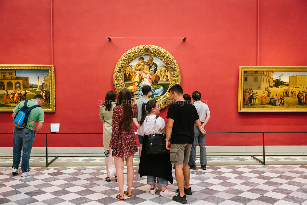 FLORENCE, ITALY - 3 JUNE 2018: Visitors are seen here by the &ldquo;Holy Family&rdquo;, also known as the Doni Tondo, that Michelangelo painted for the Doni couple around 1503-1504,  here in room 35 of the Uffizi before being relocated to room 41, in Florence, Italy, on June 3rd 2018.<br /> <br /> As of Monday June 4th 2018, Room 41 or the &ldquo;Raphael and Michelangelo room&rdquo; of the Uffizi is part of the rearrangement of the museum's collection that has<br /> been defining Uffizi Director Eike Schmidt&rsquo;s grander vision for the Florentine museum.<br /> Next month, the museum&rsquo;s Leonardo three paintings will be installed in a<br /> nearby room. Together, these artists capture &ldquo;a magic moment in the<br /> first decade of the 16th century when Florence was the cultural and<br /> artistic center of the world,&rdquo; Mr. Schmidt said. Room 41 hosts, among other paintings, the dual portraits of Agnolo Doni and his wife Maddalena Strozzi painted by Raphael round 1504-1505, and the &ldquo;Holy Family&rdquo;, that Michelangelo painted for the Doni couple a year later, known as the<br /> Doni Tondo.