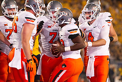 Oct 10, 2015; Morgantown, WV, USA; Oklahoma State Cowboys running back Rennie Childs (23) celebrates with teammates after scoring a touchdown during the second quarter against the West Virginia Mountaineers at Milan Puskar Stadium. Mandatory Credit: Ben Queen-USA TODAY Sports