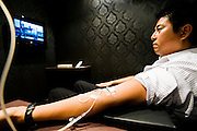 """Michito Seno, 41, an executive manager with a top securities trading company, watches TV while getting a vitamin fix at Tenteki10  in Tokyo, Japan. """"I have tried other types of vitamins and supplements, but none of them seem to be as effective as a drip. It really does have an immediate impact."""".Photographer: Robert Gilhooly"""