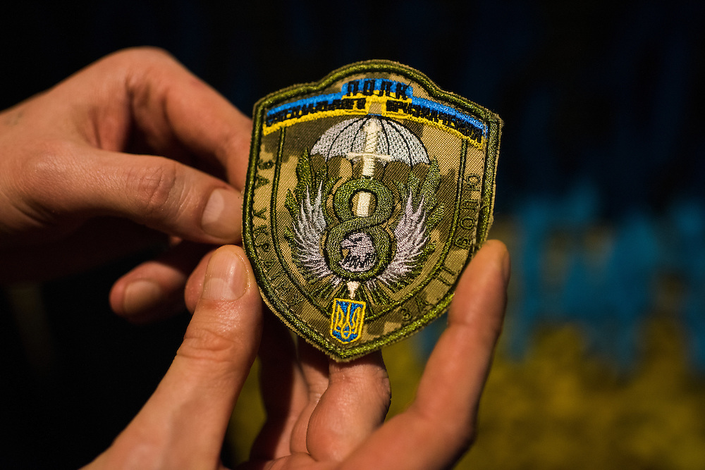 Kirill Deyneka, a veteran of the 8th Special Forces Regiment, displays his unit's insignia at Veterano Pizza on January 23, 2016 in Kiev, Ukraine. The pizza restaurant features a shelf that houses patches and other ephemera from the war in Eastern Ukraine. (Pete Kiehart for The New York Times)