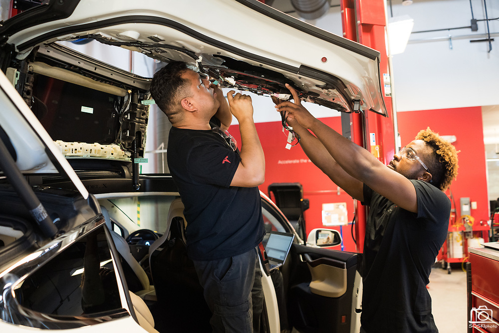 Gerard Quevedo of Perris, left, and Rakee Cromwell of Philadelphia works on a Tesla Model X door during the Tesla Start class at Evergreen Valley Community College in San Jose, California, on August 8, 2019. (Stan Olszewski for Silicon Valley Business Journal)