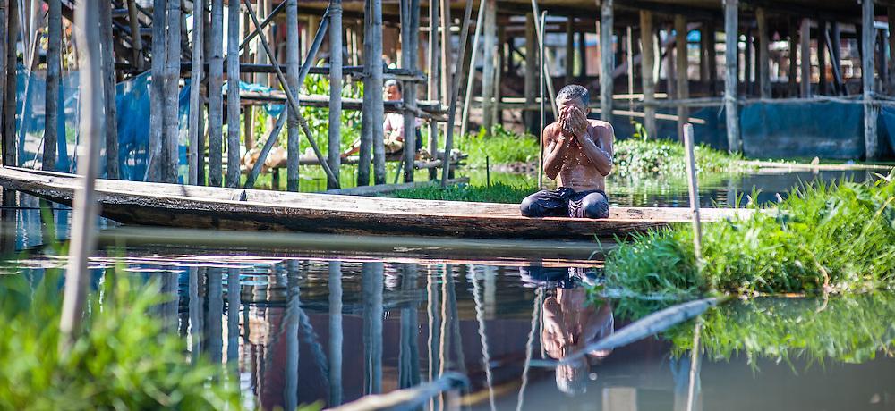 Man washing on a boat in Inle Lake (Myanmar)
