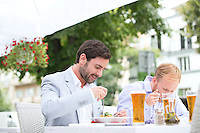 Businessmen eating food at outdoor restaurant