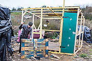 An Afgan man builds a frame for a basic shelter to protect him and his friends from the winter.