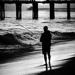 Newport Beach California sunset fishing picture. Man fishing during sunset along the Pacific Ocean shoreline om Balboa Peninsula in Newport Beach California. Balboa Pier and Newport Pier are in the background.
