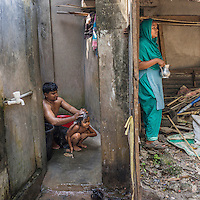 Rozina stands by the bathroom where her husband giving bath to their daughter.<br /> <br /> Rozina Akhter, 30, originally from Manikganj, was stuck under a beam during the Rana Plaza incident. The beam fell down on her waist and she fainted. After some time, she woke up to notice she could not move. She did not realize then this would be the turning point for her life, as she will have difficulties doing anything with the same ease as she once had before.She shares, &quot;Before the Rana Plaza accident, I earned my own money and lived my life in my own way. But now I am stuck at home as a handicapped person. I cannot do anything without the help of another person. Before, I had a good life, I did my work on my own, I earned money and I took care of everything but now I cannot function alone. I need help from my mom and sister in every single thing I do&mdash;even household chores. If I want to carry a heavy bag with groceries, I cannot even do that. I have to ask help from my husband. I feel really bad about this. Sometimes I feel like dying rather than living this life of constantly taking help from people.&quot; Although she is handicapped and struggles to complete small daily tasks, she tries to do as much as she can, from cooking meals for her family to getting her daughter ready for school in the mornings.