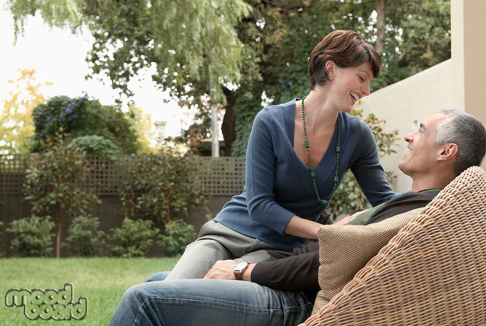 Woman sitting on husband's laps in garden
