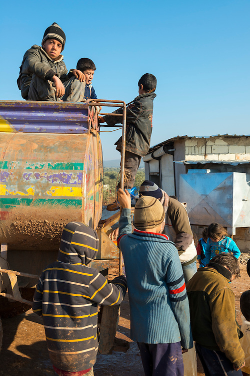 Syrian children, some with empty plastic containers, wait around a water truck in the camp for displaced persons in Atmeh, Syria. With no infrastructure in the camp, trucks are needed to deliver water to people.