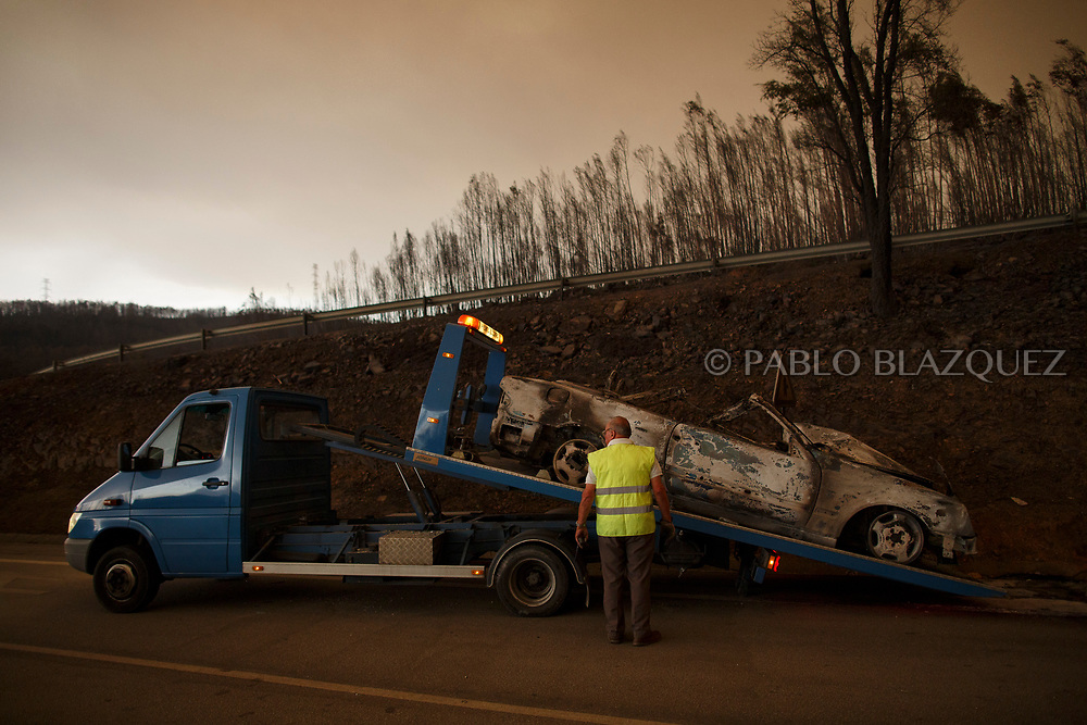 LEIRIA, PORTUGAL - JUNE 18:  A workers picks up a burned car from the road after a wildfire took dozens of lives on June 18, 2017 near Castanheira de Pera, in Leiria district, Portugal. On Saturday night, a forest fire became uncontrollable in the Leiria district, killing at least 62 people and leaving many injured. Some of the victims died inside their cars as they tried to flee the area.  (Photo by Pablo Blazquez Dominguez/Getty Images)