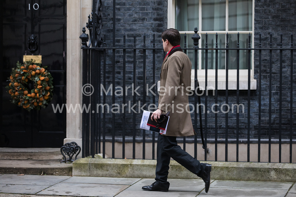 London, UK. 16 December, 2019. A male carrying a publication entitled 'Global Britain: A Twenty-First Century Vision' produced by the Henry Jackson Society arrives at 10 Downing Street on the day of a small Cabinet reshuffle following the Conservatives' general election victory.