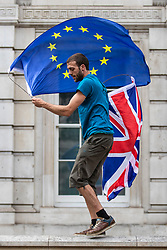© Licensed to London News Pictures. 31/08/2019. London, UK. A protester waves the EU and Union Jack flags as thousands gather outside Downing Street to protest against the suspension of Parliament. The Queen has approved Prime Minister Boris Johnson's request to prorogue Parliament shortly after MPs return to work in September, a few weeks before the Brexit deadline of 31 October. Photo credit: Rob Pinney/LNP