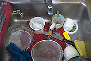 kitchen sink with cups and other dirty kitchen utensils