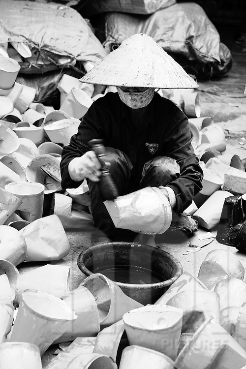 Woman painting a serie of devotive objects. She wears the conic hat and gloves to protect her hands from the paint.