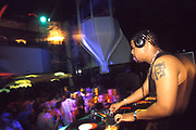 DJ Felix Da Housecat on the decks with a crowd dancing in the background. UK 1990's