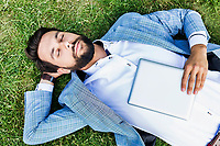 Portrait of young attractive businessman holding digital tablet while sleeping and lying on the grass