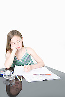 Cute girl studying at table over white background
