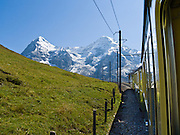 "The mountain peaks of Eiger and Mönch (Ogre and Monk) rise above Wengernalpbahn cog train in Lauterbrunnen Valley, Berner Oberland, Switzerland, the Alps, Europe. Wengernalpbahn, the world's longest continuous rack and pinion railway, goes from Grindelwald up to Kleine Scheidegg and down to Wengen and Lauterbrunnen. From Kleine Scheidegg, another cog train (Jungfraubahn) ascends steeply inside the Eiger to Jungfraujoch, the highest railway station in Europe. A gondola (gondelbahn) connects Grindelwald with Männlichen, where a cable car goes down to Wengen (Luftseilbahn Wengen-Männlichen). The Bernese Highlands are the upper part of Bern Canton. UNESCO lists ""Swiss Alps Jungfrau-Aletsch"" as a World Heritage Area (2001, 2007)."
