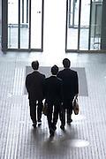 3 businessmen leaving an large office building