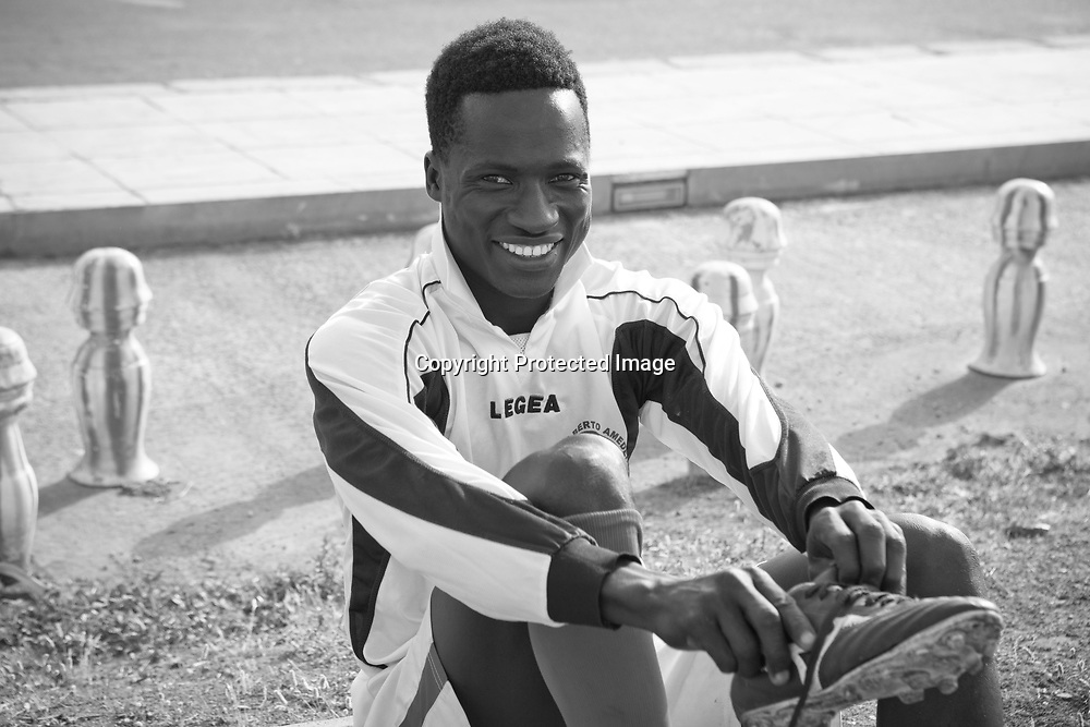 Ebrima 17 years old from Gambia, getting ready to play soccer at the beach front in Palermo, Sicily